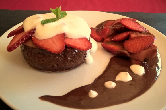Chocolate cake stuffed with chocolate mousse with whipped cream and fresh strawberries