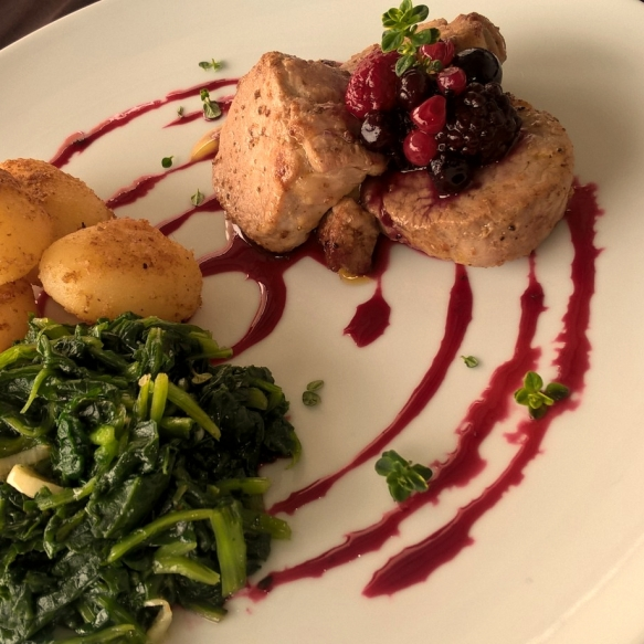 Pork loin medallion with a wild berries reduction with sauteed turnip greens and potatoes