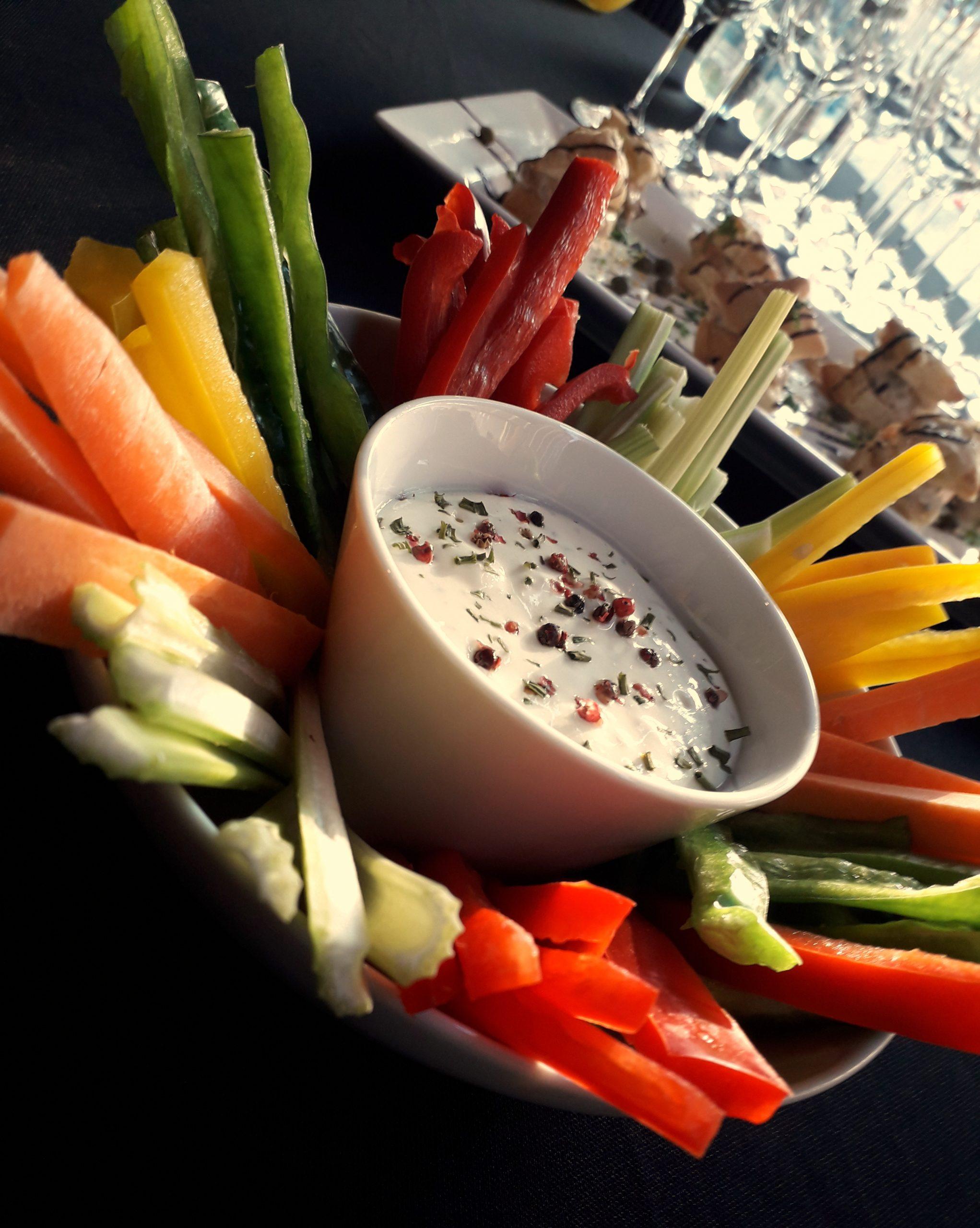 Tiras de legumes variados com tijelas de molho de iogurte com queijo